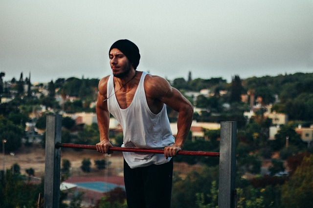 Man in his twenties wearing a white vest, jeans and a dark beanie hat is using outdoor gym equipment. He is pushing himself up on a metal bar to show how calisthenics is good for strength training. In the background there is a suburban town.