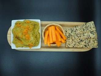 white square bowl of carrot and coriander hummus topped with grated carrot. next to it is a round wooden bowol filled with carrot sticks and three seeded flatbreads. they are lined up on a wooden flat plate and set against a black background