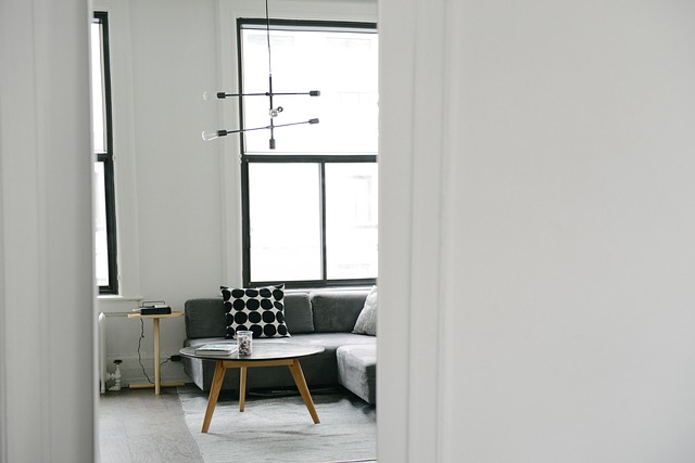 looking through a white doorway into a very modern wiary white living room that looks clean and fresh