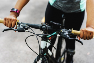 Close up of a bike's handlebars with a person sat on the bike to indicate the health benefits of cycling