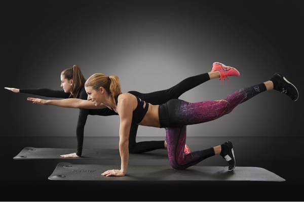 Two women exercising together set against a black background. They are on their knees with one lef stretched out behind them and the opposite arm stretched out in front of them.