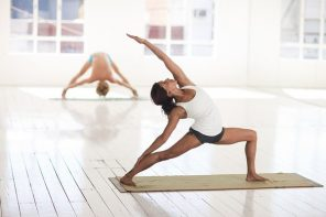 Woman doing a yoga stretch as part of her fuctional fitness training she is in a studio and there in another woman streching out in the background.