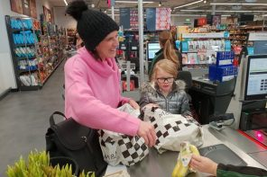 Mum and daughter doing a healthy family food shop at Marks and Spencer. They are at the till putting some bananas in a carrier bag. Mum is wearing a black bobble hat and a pink jumper and is smiling. Daughter is wearing a silver puffa jacket and is wearing glasses.