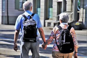 an older coupl holding hands stood with their backs to the camera. They both have black rucksakcs and look as though they are exploring a foreign city together in retirement.