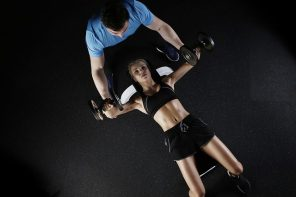 woman in black gym kit lying on her back lifting hand held weights and being supported by a man in a blue t shirt.