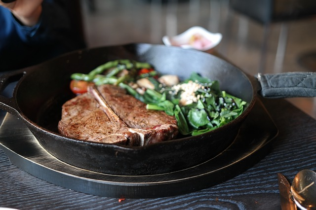 Blac k frying pan containing a t-bone steak and green vegetables