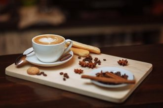 cappucino coffee in a white cup on a wooden board with scattered coffee beans and biscuits