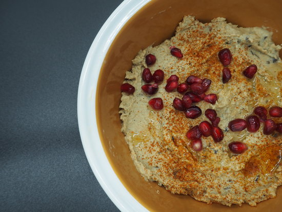 Close up of a bowl of smoked aubergine hummus garnished with pomegranate seeds and dusted with smoked paprika