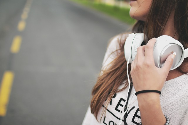 Close up of the side of a teenage girl with long dark hair and white headphones round her neck. there is a road in the back ground.