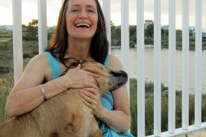 Middle aged woman sat cuddling her dog and laughing. She looks younger than she is and really happy and full of life. She is wearing a bright blue sleeveless dress and leaning against some white railings which look out over a lake.