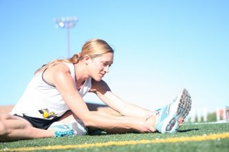 Blonde haired femaie in her twenties sitting and stretching out her legs on an athletics track after having trained like a professional athlete