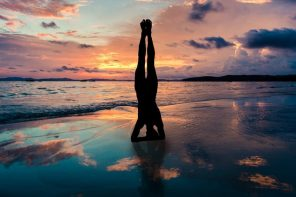 silhouette of a woman doing a yoga headstand on a sunset beach