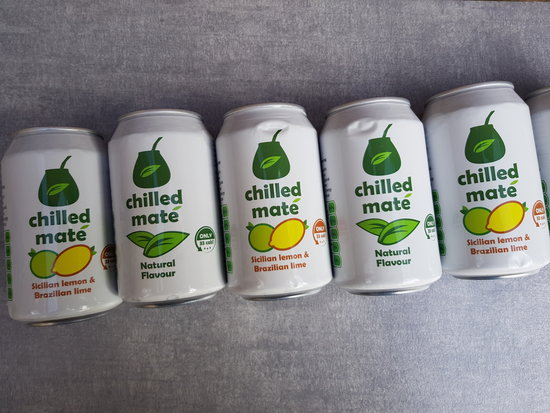 5 cans of Chilled Mate Yerba Energy Drinks laid flat in a diagonal line across a light slate grey background