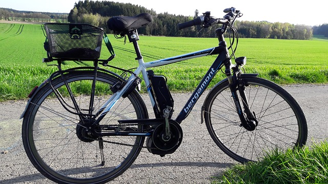 A black and white e-bike stood up in the middle of a country road. There is a green field and woodland in the background and it is a sunny day, perfect for cycling to work.