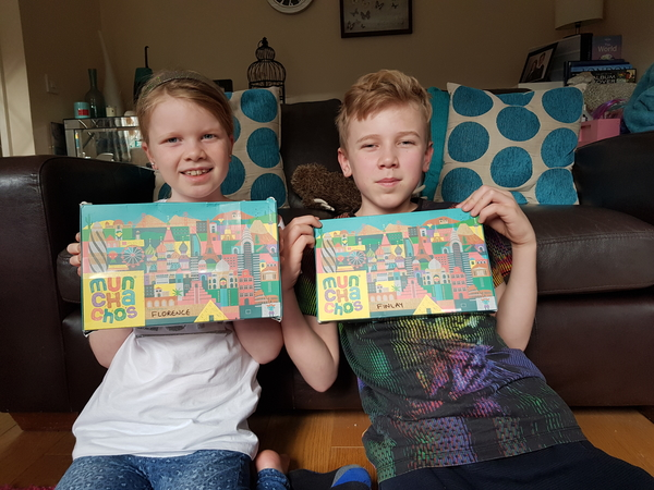 2 children, one girl and one boy sat in a living room holding up 2 boxes of Munchachos snack boxes for kids