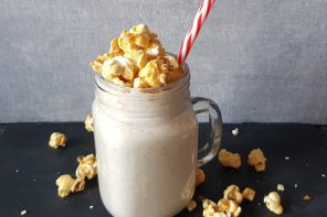 Pecan Pie smoothie in a mason jar mug topped with popcorn and a red and white striped straw