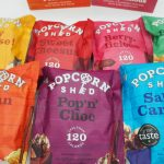 7 packets of Popcorn Shed gourmet popcorn laid out on a white background ready for review