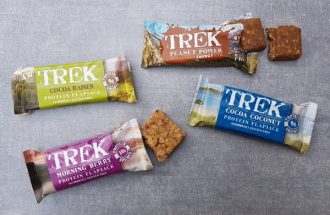 A selection of 4 Trek protein flapjacks and protein energy bars laid out on a light grey slate background. 2 packets are open revealing the bars and the other two are closed.