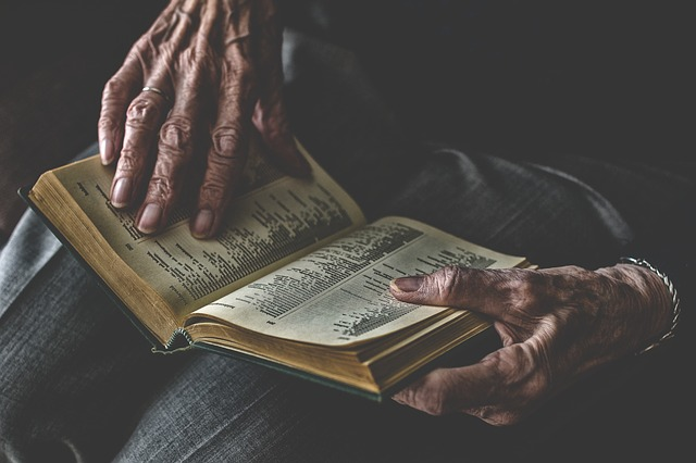 Close up of an old mans wrinkjly hands holding an open book