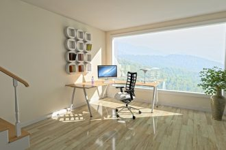 A light airy room with a massive wqindow overlooking a beautiful vista. The room has light wooden floors and cream walls and there is a corner desk with a computer on it and a chair. On the wall is a piece of angular white wall art. It looks like a very unclutteered tranquil space.