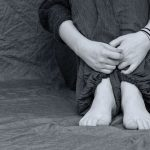 black and white image of someones hand feet and knees sat scrunched up clutching themselves