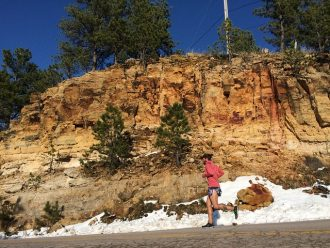 Male runner running on a road alongside a rocky embankment. There is snow at the side of the road suggesting it is cold but he has still got the motivation to get outside and exercise.
