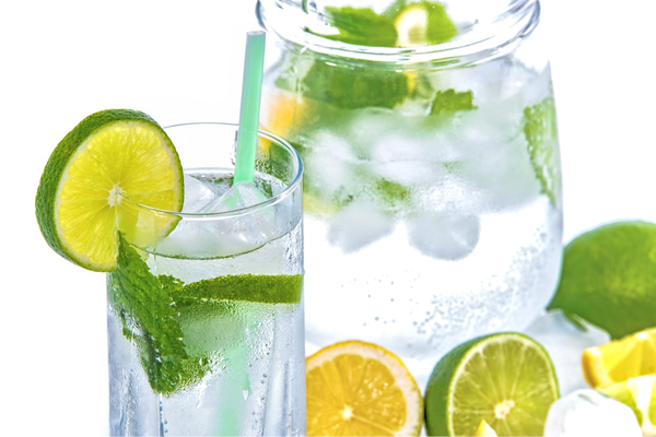 glass filled with clean filtered water with a mint leaf, ice cubes a green straw and a slice of lime on the side. There is a clear glass jug filled with the same contents in the background and there is hald a sliced lemon and lime next to the glass.