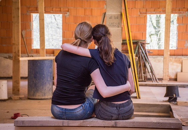 Two femasle friends sat side by side with their backs to the camera. they ahve their arms around one another to help support and show their friendship. They are in what looks like a garage or work room.