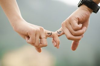 close up of a male and female hand joined by interlocking middle fingers. the woman is wearing a ring and the man has on a wrist watch. On their middle fingers they both had small tattoos of an achor showing they work hard at keeping their relationship strong.