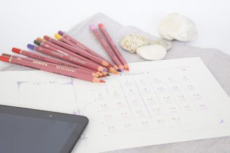 a white calendar sheet laid out on a desk with some coloured pencils the corner of a tablet device and some pebbles