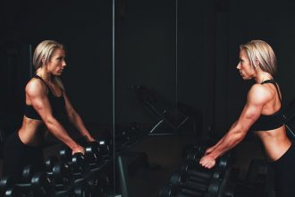 blonde haired woman looking at herself in a mirror. She has big muscles and is about to do some wieght lifting as there are a selection of hand weights in front of her. She likes to look good at the gym.