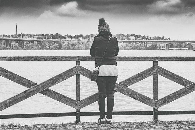 blacl and white photo of a woman stoof with her back to the camera on a pier overlooking the sea.