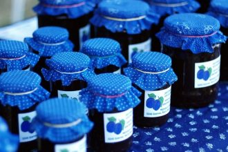 rows of organic plum jam in jars with purple cloth lids and hand printed labels