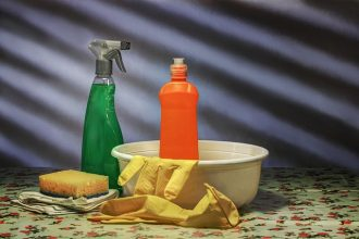 selection of cleaning materials on a table - including yellow rubber gloves, a green spray bottle, an orange squirty bottle and a sponge