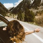 Brunette woman leaning out of the front of the car stretching her arm out. She is driving along a highway through the mountains and it is a beautiful sunny day. She is enjoying travel as a means of self care and reflection.