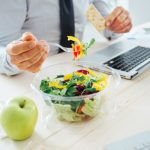 Close up of a bowl of salad on a` desk nexy to a computer kepboard and an apple. There is an male office workers torso and arms in shot, he is hokding a forful of salad in his left hand.