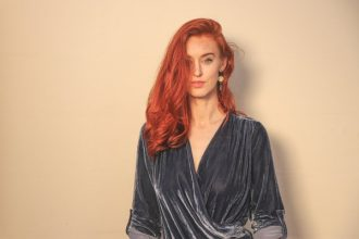 Long haired red headed woman standing against a plain neautrl background, wearing a mid grey velvet v necked long sleeved top.