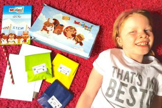 a young blonde haired girl lying on a pink rug next to the contents of the Weekend Box Club craft kits she has just received through the post