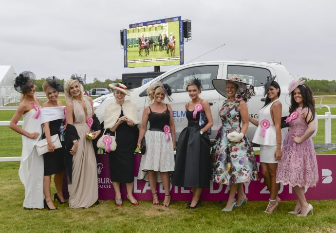 9 ladies dressed up for the horse races stood in front of a car and there is a TV screen with horces racing on it in the background.