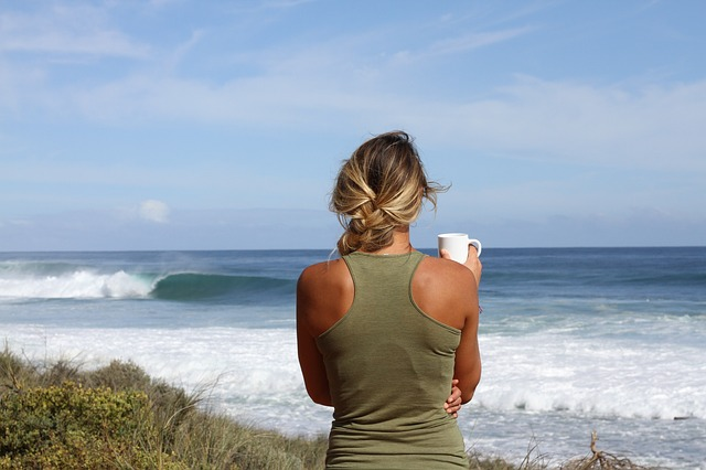 woman stood with her back to the camera looking out towards the ocean. She is holding a white coffee cop, her blonde hair is plaited to one sdie and she is wearing a khaki green racer back vest.