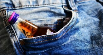 small bottle of brandy poking out of the pocket of a pair of blue jeans suggesting the person had addiction issues