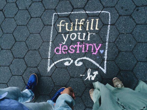 looking down to a dark tiled floor on which the words fulfill your destiny have been written in yellow and pink chalk