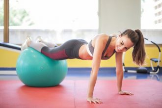 Young woman in gym kit doing a press up while her legs are resting on a green exercise ball
