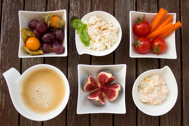 A selection of healthy foods including tomatoes, figs, hummus laid out in 6 white bowls on a wopoden surface