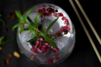 Photo taken from above looking down on a gin cocktail decorated with a herb sprig and pomegranite seeds