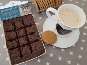 Horsham gingerbread in it's tray packet with a mug of cappucino on a plate and some biscuits