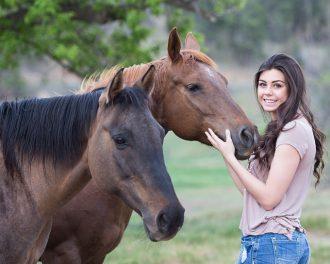 brunette girl in her twenties stood next to two brown horses