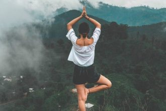 Woman stood on the edge of a mountain doing a yoga stand on one leg looking out across the jungle landscape