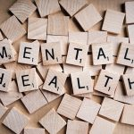 wooden scrabble tiles spelling out the words mental health
