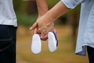 man and woman holding hands with two baby shoes hanging off of their little fingers